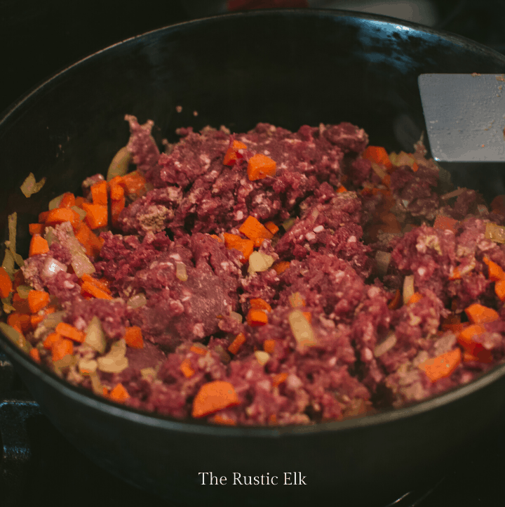 Ground venison is added to the pan.