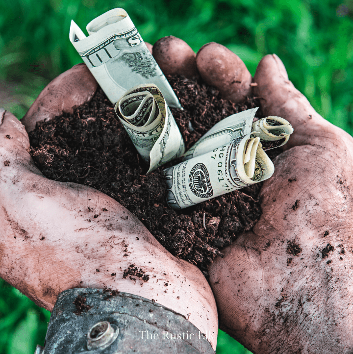 Man holding dirt and money in his hands. You can make money on your homestead with a little ingenuity.