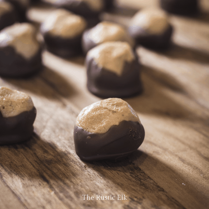 Peanut butter buckeye balls on a board.