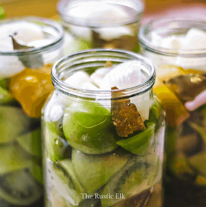 Jar of pickled green tomatoes on a table.